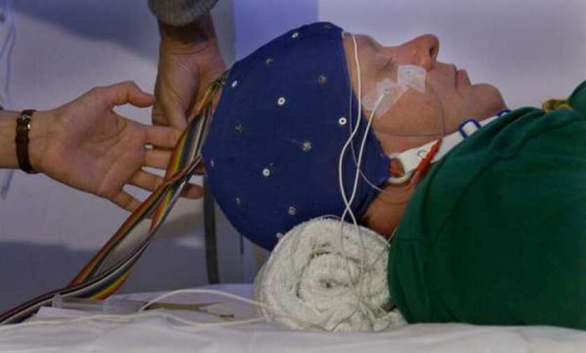 A patient is fitted with an electroencephalogram cap.
