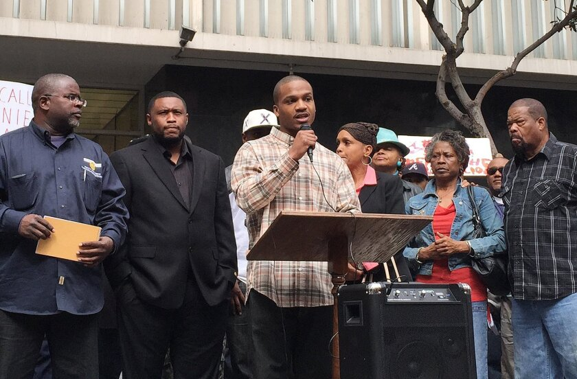 Aaron Harvey, who is one of many being charged under a gang conspiracy law, speaks at a rally in front of the San Diego Superior courthouse on Feb. 27, 2015, before a court hearing. Co-defendant Brandon Duncan, second from the left, stands behind him in support. Photo by Kristina Davis