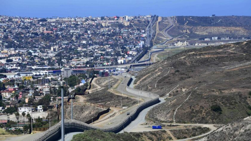 Construction to replace the shorter, brown barrier closer to Tijuana began Friday along a 14-mile stretch of the San Diego border. Congress has funded projects to replace both rows of fencing in this part of the U.S.-Mexico border.