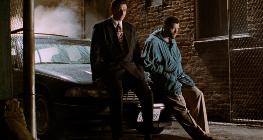 Two men lean on the hood of a car in an alley.