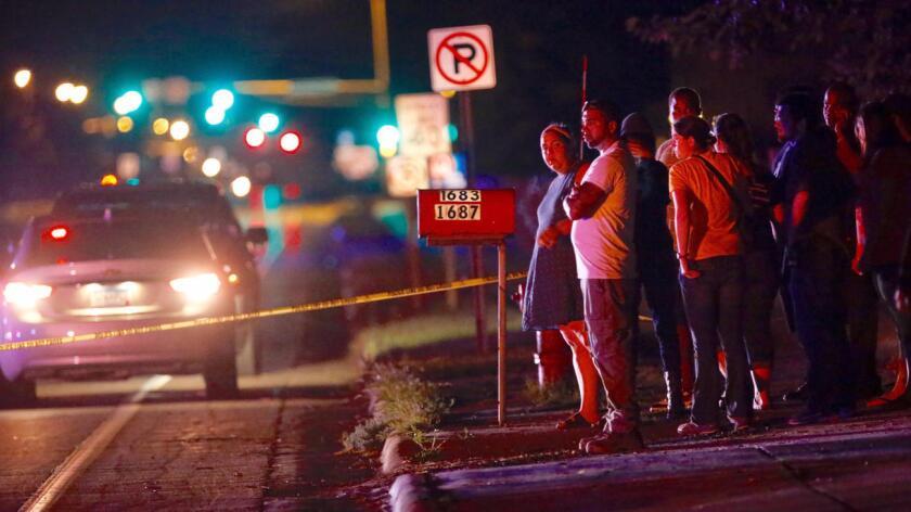 """En el video, la mujer dice a la cámara que """"la policía acaba de disparar a mi novio sin motivo aparente"""". En la foto, curiosos son testigos de los momentos en que el vehículo es detenido y el ofaparentemente baleado por un oficial."""