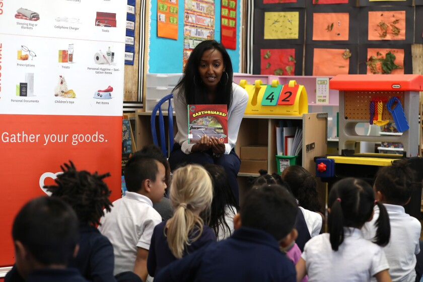 A teacher reads to elementary school students in a classroom
