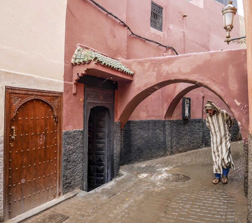 FEZ, MOROCCO - A man in a djellaba, a long, loose-fitting robe, ducks under one of the many archways