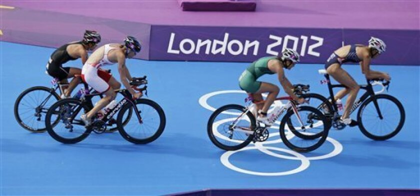 United States' Laura Bennett leads a group of triathletes during the bike portion of the triathlon at the 2012 Summer Olympics, Saturday, Aug. 4, 2012, in London. (AP Photo/Charlie Riedel)
