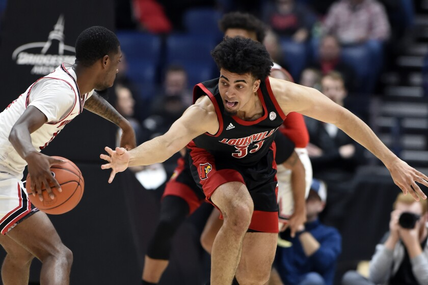 Louisville forward Jordan Nwora (33) reaches for the ball as he tries to knock it away from Western Kentucky guard Taveion Hollingsworth (11) during the second half of an NCAA college basketball game Friday, Nov. 29, 2019, in Nashville, Tenn. (AP Photo/Mark Zaleski)