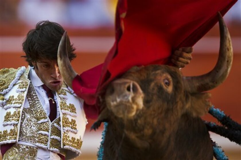 """Spanish bullfighter Antonio Nazare performs with an Alcurrucen fighting bull during a bullfight of the San Fermin festival, in Pamplona, Spain, Sunday, July 7, 2013. Revelers from around the world arrive to Pamplona every year to take part on some of the eight days of the running of the bulls glorified by Ernest Hemingway's 1926 novel """"The Sun Also Rises."""" (AP Photo/Daniel Ochoa de Olza)"""