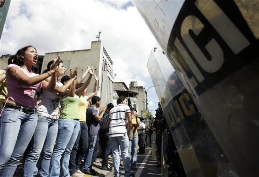 Students protest in front of police after tear gas containers were thrown in three locations in Caracas, Monday, Jan. 19, 2009.  Unidentified aggressors hurled tear gas canisters at a gathering of university students, the Vatican's diplomatic mission in Venezuela and the home of a media executive o
