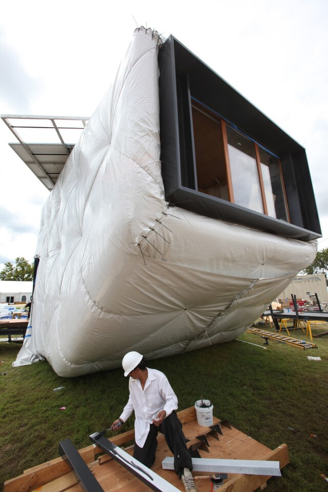 A member of the team from Caltech in Pasadena and the Southern California Institute of Architecture in Los Angeles works on CHIP, the Compact Hyper-Insulated Prototype, during the U.S. Department of Energy Solar Decathlon in Washington, D.C.