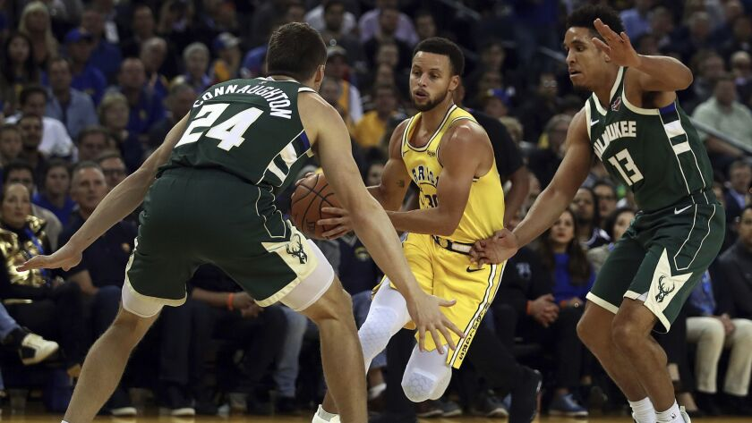 Golden State Warriors' Stephen Curry, center, drives the ball between Milwaukee Bucks' Pat Connaughton (24) and Malcolm Brogdon, right, during the first half.