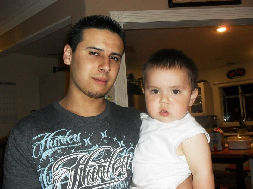 Jacob Wallis, photographed in 2010, with his toddler son, Izaiah, just months before Izaiah was struck by a teenage drunk driver and left severely disabled.