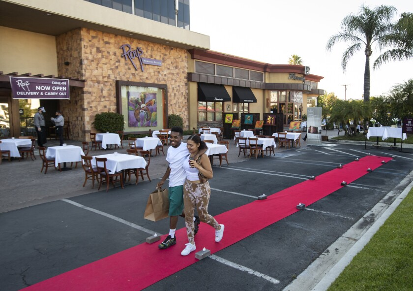 A couple leaves Fleming's Prime Steakhouse after dining outdoors in Woodland Hills on July 17.