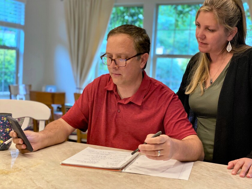 Chris Maddox and his wife, Heather Maddox, work on lyrics to one of their coronavirus-themed parody songs. It takes them about two hours to come up with the new lyrics for a song.