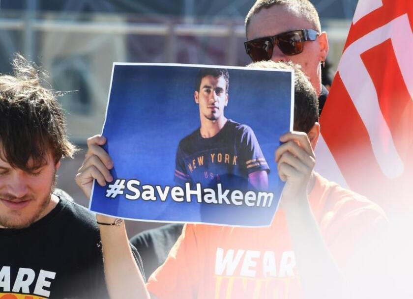 Un hombre muestra un cartel con la foto del futbolista bareiní Hakeem Al-Araibi durante una protesta para pedir su puesta en libertad el pasado viernes en Sídney. EFE