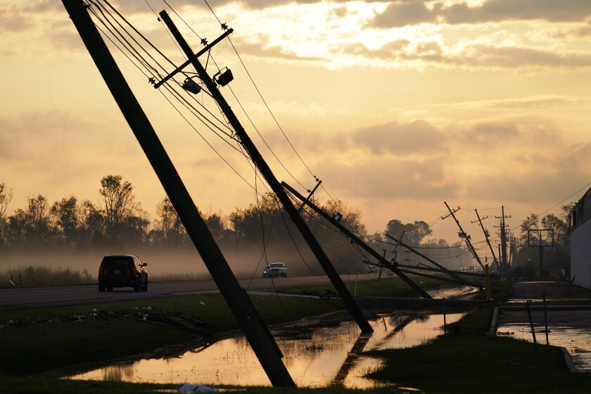 Downed power lines slump over a road in the aftermath of Hurricane Ida, Friday, Sept. 3, 2021, in Reserve, La. (AP Photo/Matt Slocum)
