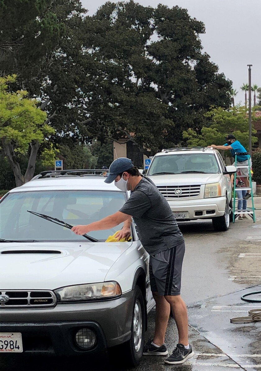 "Volunteers offered free car washes at the Village Church ""Drive-By Drop-Off"" event on Sept. 26."