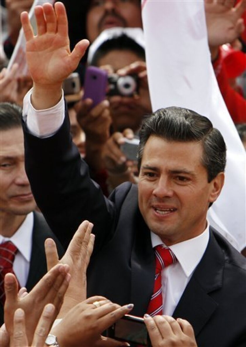 FILE - In this Nov. 27, 2011 file photo, Enrique Pena Nieto, former governor of Mexico state and presidential candidate for the Institutional Revolutionary Party, PRI, waves to supporters during a rally in Mexico City.  Pena Nieto, the leading contender for Mexico's presidency, has raised criticism