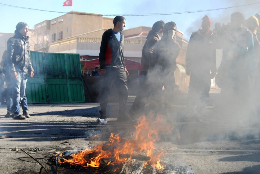Tunisian youths in the central town of Kasserine burn debris as they protest against the Islamist party Ennahda and against the country's persistent economic crisis.