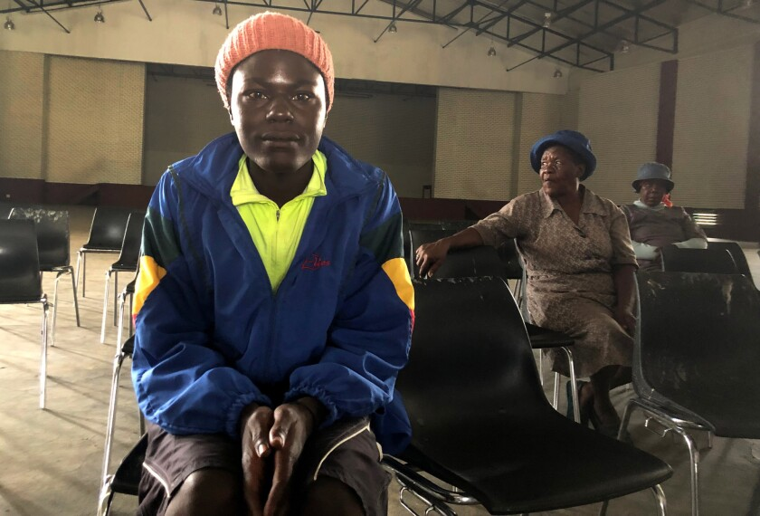 James Mashakeni, left, and Grace Pitse, middle, attend a meeting in a community hall in Brits, South