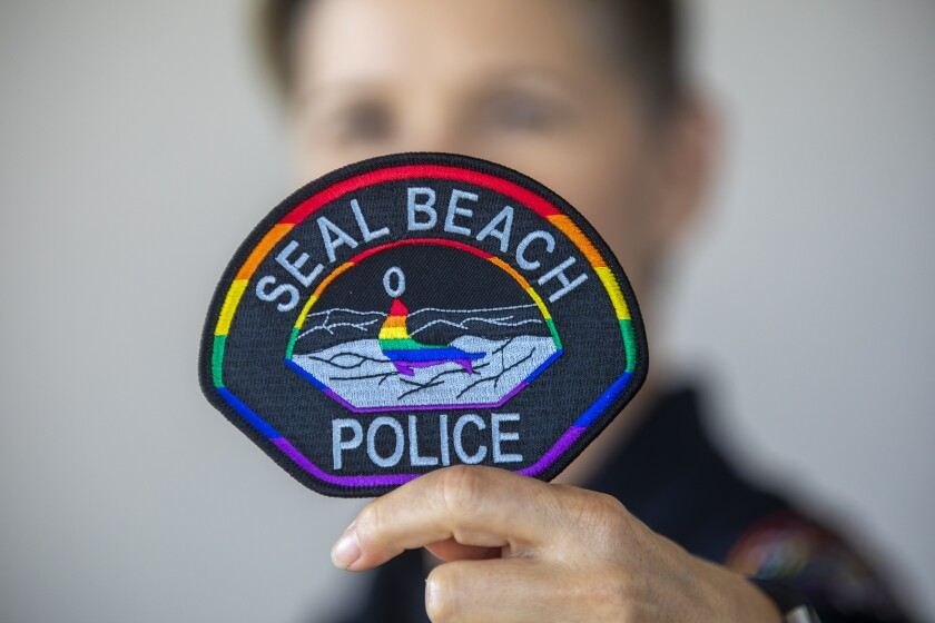 Seal Beach Police Officer Erin Enos holds a rainbow patch.