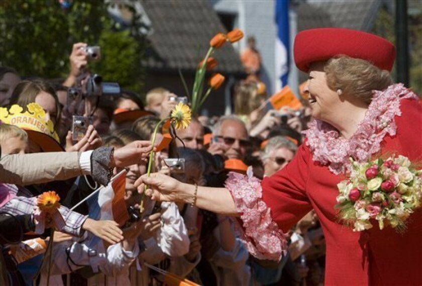 Queen Beatrix of the Netherlands greets well wishers, shortly before a car ploughed into the crowd, during festivities marking Queen's Day in Apeldoorn, Netherlands, Thursday, April 30, 2009. Dutch authorities say a speeding car that raced toward an open bus carrying Dutch Queen Beatrix and her family during a holiday parade has killed four people and injured 13 others. Prosecutors said the incident was deliberate, but not an act of terrorism. The small black car was heading at high speed toward the royal bus and passed within a few meters of it before plowing into a stone monument. Police declined to identify the driver beyond saying he was a white Dutch male, aged 38, who had no police record or history of mental illness. (AP Photo/Robin Utrecht, Pool)