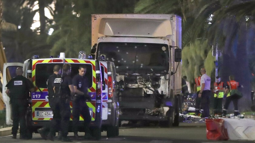 Police officers and rescued workers stand near a van that ploughed into a crowd leaving a fireworks display in the French Riviera town of Nice on July 14, 2016.