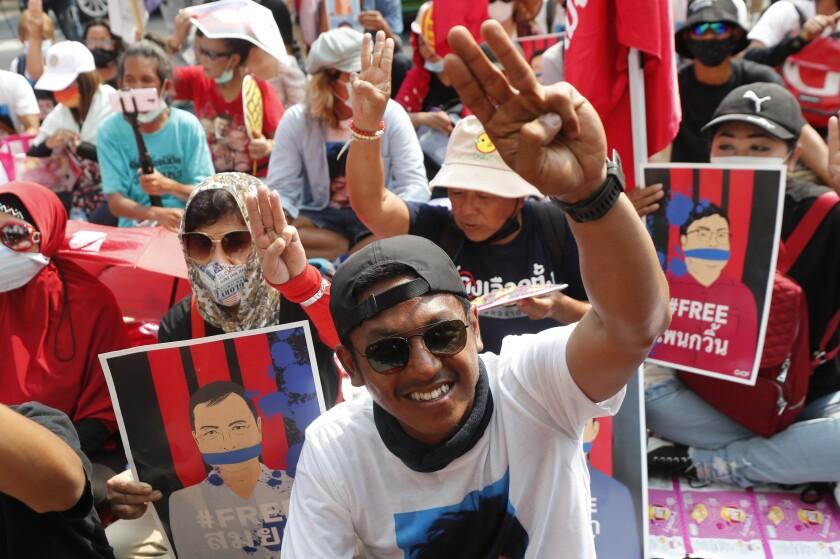 El activista prodemocracia Jatupat Boonpattararaksa hace un gesto con tres dedos que se ha convertido en un símbolo de las protestas a su llegada a la fiscalía en Bangkok, Tailandia, el lunes 8 de marzo de 2021. La fiscalía tailandesa presentó cargos de sedición contra 18 manifestantes, y añadió cargos de injurias a la corona para tres de ellos, incluido Jatupat. (AP Foto/Sakchai Lalit)