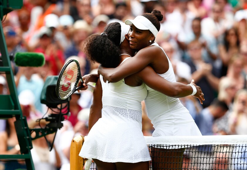 Sisters Serena Williams and Venus Williams share a hug after their fourth-round Wimbledon match last summer