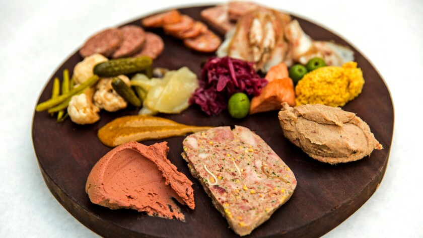 A plate of truffled chicken liver, terrine de campaign, rillettes, mustard, testa, liverwurst, andouille, smoked beef deckle, house pickles and olives at Terrine.