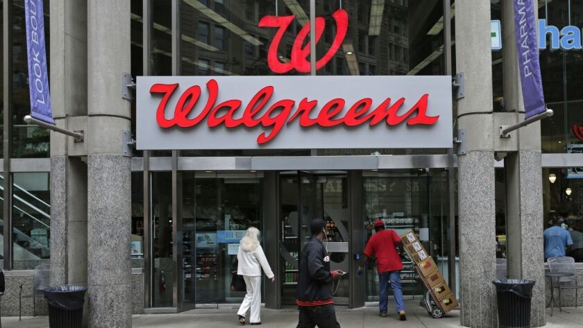 FILE - In this June 4, 2014, file photo, people walk in to a Walgreens retail store in Boston. Walgr