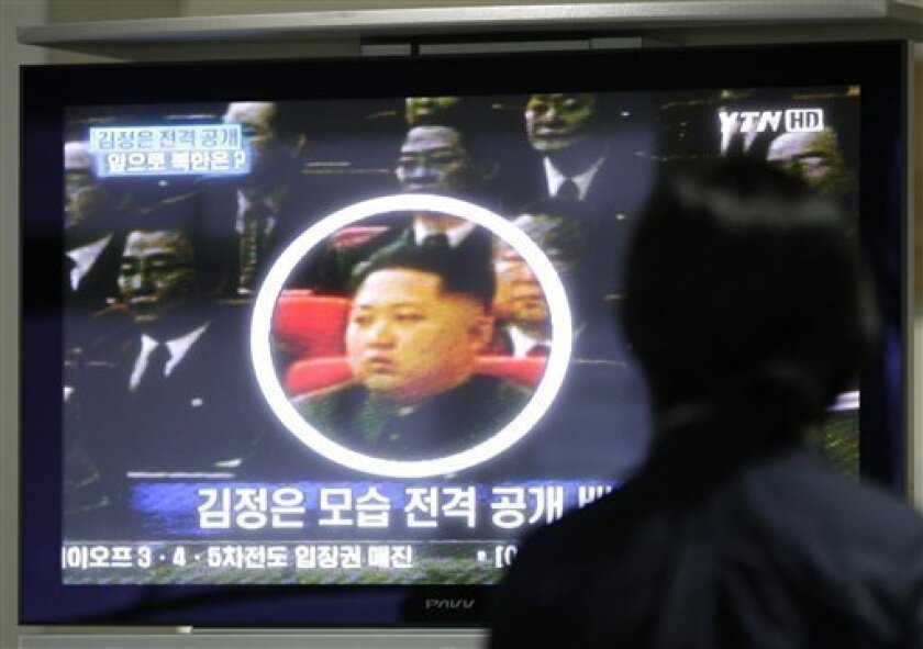 FILE - In this Oct. 1, 2010 file photo, a South Korean worker watches a TV news program showing North Korean leader Kim Jong Il's third son Kim Jong Un as she waits to head to the North Korean city of Kaesong at the customs, immigration and quarantine office for North Korea near the Demilitarized Zone (DMZ) of Panmunjom in Paju, South Korea. North Korean authorities confirmed to TV news agency APTN in Pyongyang that the man shown in the footage is Kim Jong Un. North Korea's heir apparent Kim Jong Un appeared Tuesday, Oct. 5, 2010 for the first time in the country's state media reports on visits by his father, supreme leader Kim Jong Il, to review troops and factories. (AP Photo/Ahn Young-joon, File)