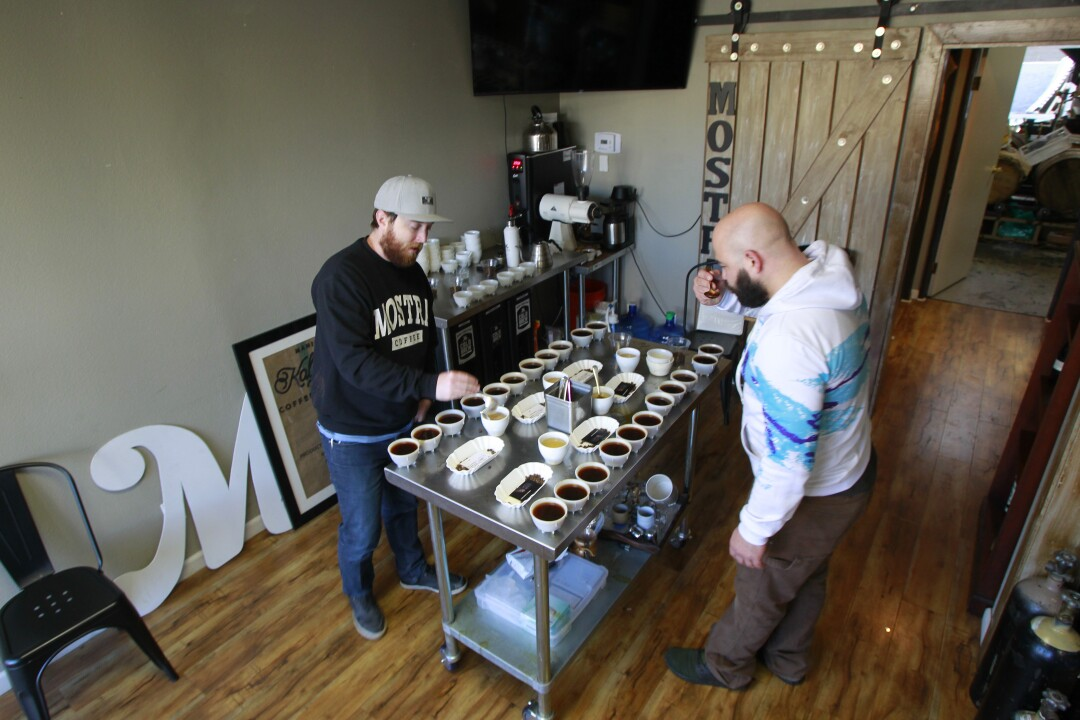 Head roaster Nick Berardi (right) and director of coffee Ryan Sullivan taste test different coffees at the Mostra roasting facility.