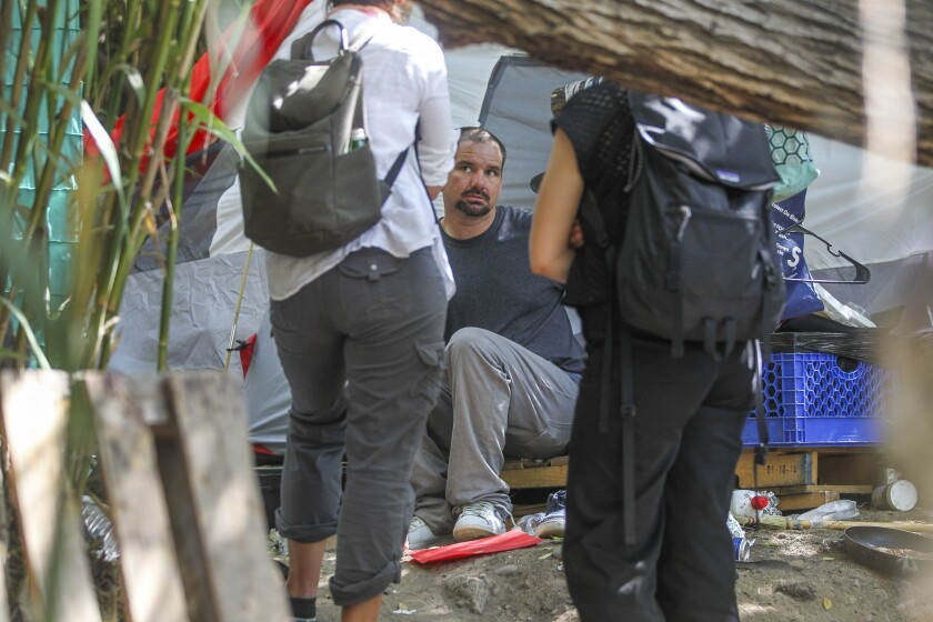 United Nations Special Rapporteur Leilani Farha, left, and her assistant Julieta Perucca talk to a homeless man at his encampment at the San Diego River riverbed Mission Valley on Tuesday, August 13, 2019.