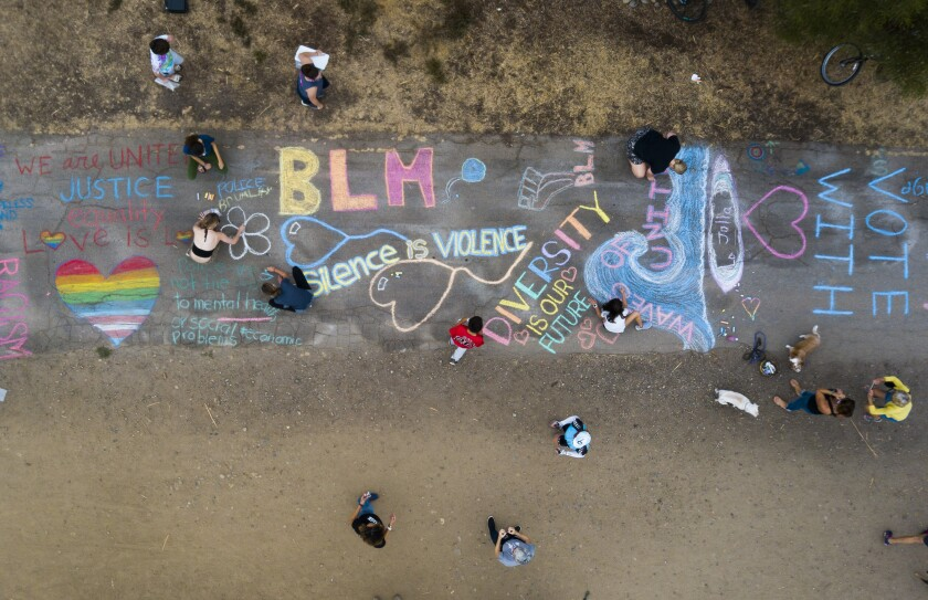 A group of parents and children gathered in La Jolla to write chalk messages in support of the Black Lives Matter movement.