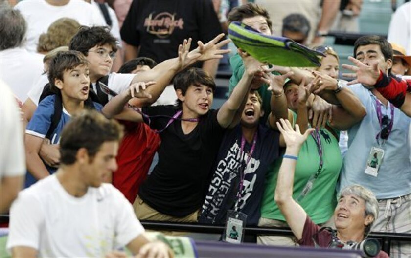 Fans try to catch a towel thrown by Juan Martin del Potro of Argentina, foreground, after he defeated Marin Cilic of Croatia 6-3, 7-6 (3) during the Sony Ericsson Open tennis tournament, Monday, March 26, 2012, in Key Biscayne, Fla. (AP Photo/Lynne Sladky)