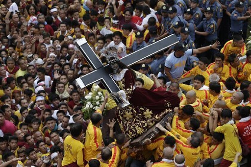 Catholic devotees jostle to get closer to the centuries-old image of the Black Nazarene in a raucous celebration on its feast day Wednesday, Jan. 9, 2013 in Manila, Philippines. The annual procession by hundreds of thousands of devotees is now becoming to be a tourist attraction. (AP Photo/Bullit Marquez)