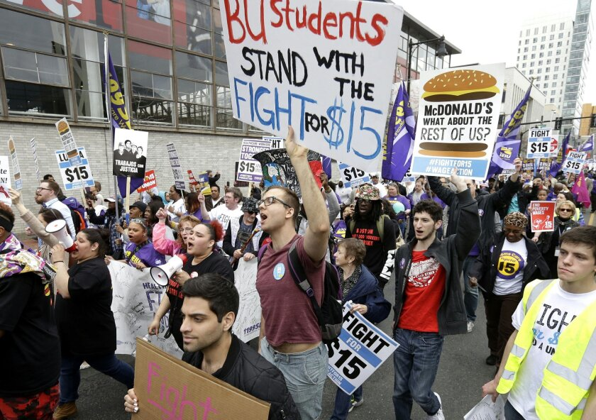 Boston University student Patrick Johnson, center, holds a sign as he joins with other protesters, including students, fast-food restaurant employees and other workers, as they march Tuesday, April 14, 2015, in Boston. Organizers of the event are calling for the nation's lowest paid workers to earn