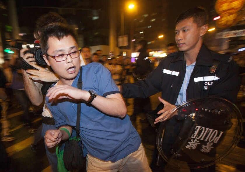 A man who authorities said was an opponent of the Hong Kong protesters is removed by police from a crowd in the Mong Kok district on Oct 23.