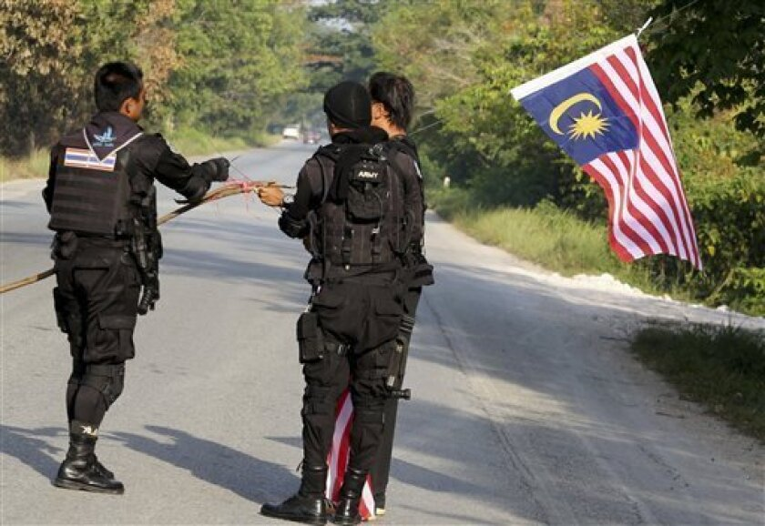 Thai rangers take down a Malaysian flag hoisted by suspected Muslim insurgents on a street in Yala province, southern Thailand, Friday, Aug. 31, 2012. Police in Thailand say insurgents have staged a wave of coordinated attacks in the Muslim-dominated south of the country, burning Thai flags and raising Malaysian flags in their place for the first time in years. Friday's attacks come on the anniversary of the 1989 founding of an umbrella separatist group, as well as the anniversary of neighboring Malaysia's independence from British rule. (AP Photo/Sumeth Panpetch)