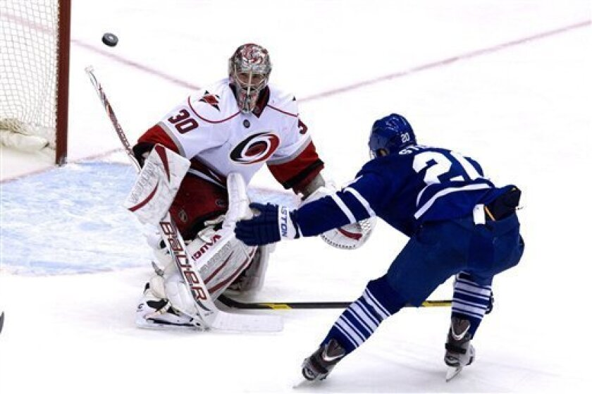 Carolina Hurricanes goaltender Cam Ward, left, stops Toronto Maple Leafs' David Steckel during the third period NHL hockey game in Toronto on Tuesday, March 27, 2012. (AP Photo/The Canadian Press, Chris Young)