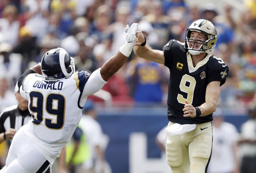Drew Brees of the New Orleans Saints injures his throwing hand as he is hit by Aaron Donald of the Los Angeles Rams during the first quarter in the game at Los Angeles Memorial Coliseum on Sunday.