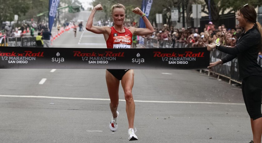 Shalane Flanagan crosses the finish line pumping her fist at the Suja Rock 'n' Roll half marathon where she finished in first place with a personal record of 1:07:51.