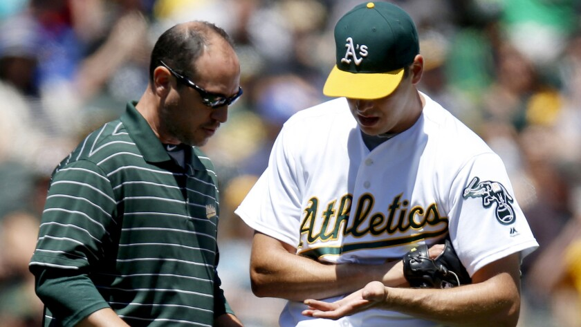 Left-hander Rich Hill has his pitching hand checked by trainer Nick Paparesta during his last start with the Oakland Athletics before being acquired by the Dodgers.