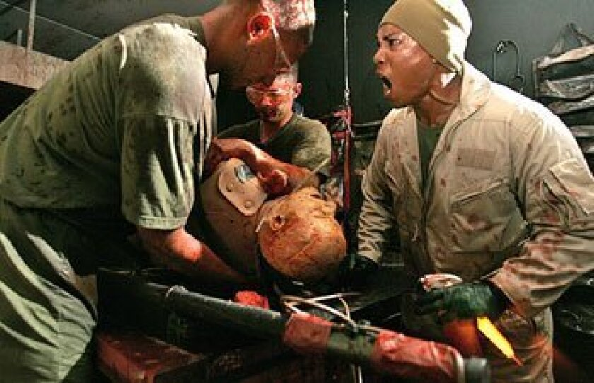 Navy corpsman Joseph Gagucas (right) yelled during training for Navy doctors Michael Sracic (left) and Jason Slingerland using a human simulator.  (File photo)