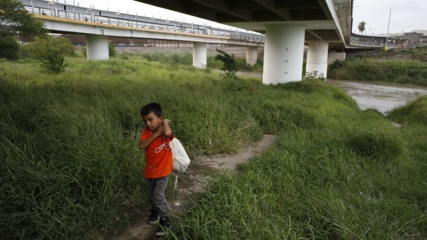 Hassan Bustio Paz, a 5-year-old from Honduras, walks with his mother and other migrants below Puerta
