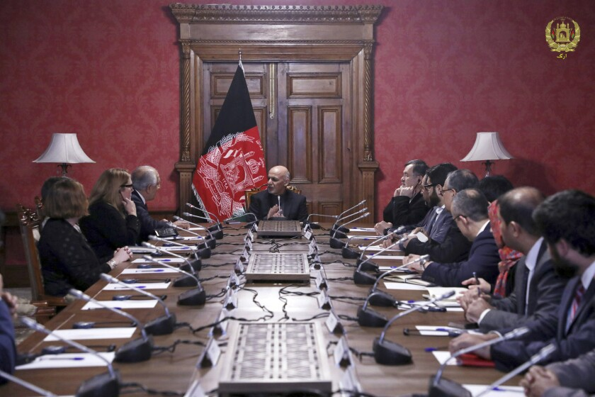 Afghan President Ashraf Ghani, center, speaks to U.S. peace envoy Zalmay Khalilzad, third from left, in Kabul in January.