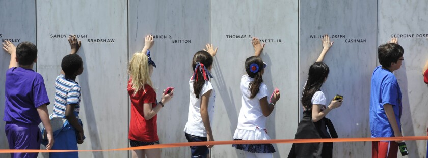 """FILE - In this May 24, 2016 file photo, fourth grade students from Baldwin-Whitehall school district near Pittsburgh, touch the """"wall of names"""" at the Flight 93 Memorial in Shanksville, Pa.,during their classroom experience. (Todd Berkey/The Tribune-Democrat via AP, File)"""