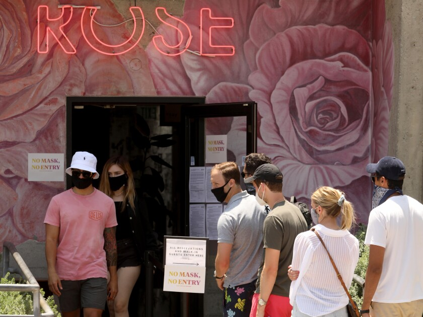 Customers wearing face masks wait in line at the Rose restaurant in Venice