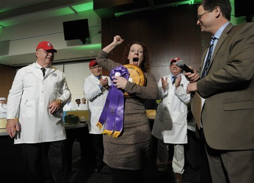 Marieke Penterman, center, owner of Holland's Family Cheese LLC in Thorp, Wis., reacts after winning first place in the U.S. Cheese Championship Contest at Lambeau Field in Green Bay, Wis., on Wednesday, March 13, 2013. Penterman's winning cheese was an aged Gouda. (AP Photo/The Green Bay Press-Gazette, Evan Siegle) NO SALES