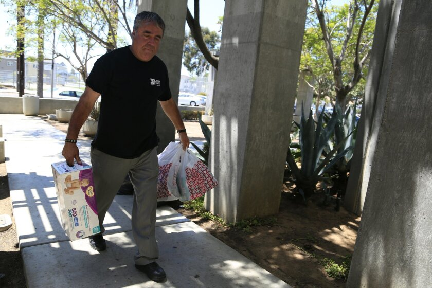Enrique Morones carries donated diapers into the offices of Border Angels.