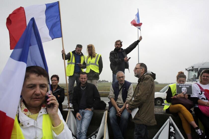 """Manifestantes sostienen banderas francesas mientras camioneros bloquean la carretera cerca de Calais, en el norte de Francia, el lunes 5 de septiembre del 2016. Cientos de camioneros, agricultores, estibadores y comerciantes bloquearon una autopista principal el lunes en el norte de Francia para exigir el cierre del campamento de migrantes en Calais, conocido como """"la jungla"""". (AP Foto/Thibault Camus)"""